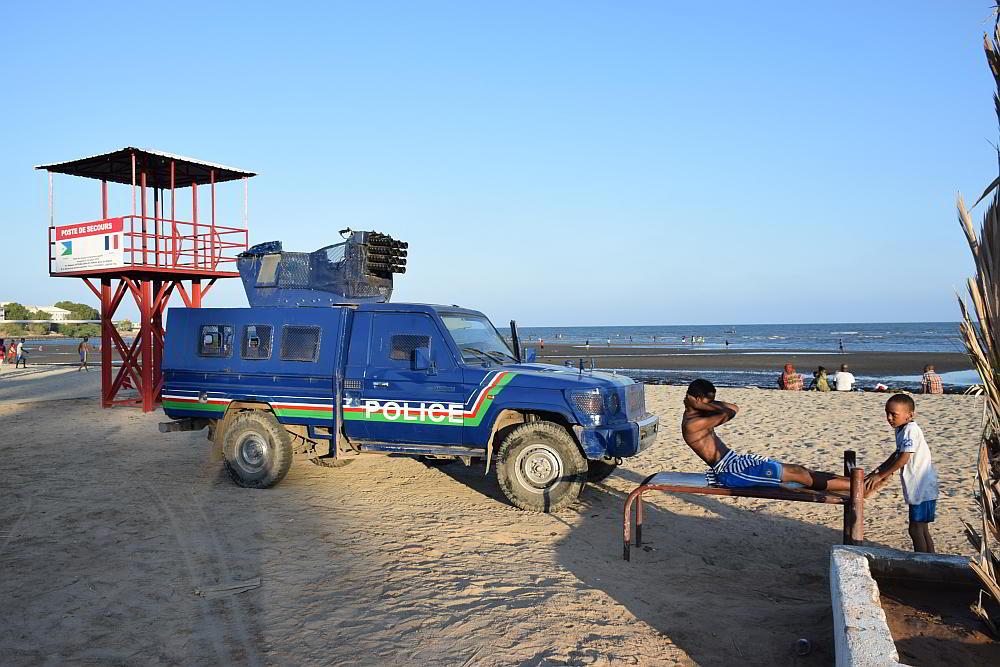 Деца спортуват пред охраняваща ги полицейска кола в Джибути